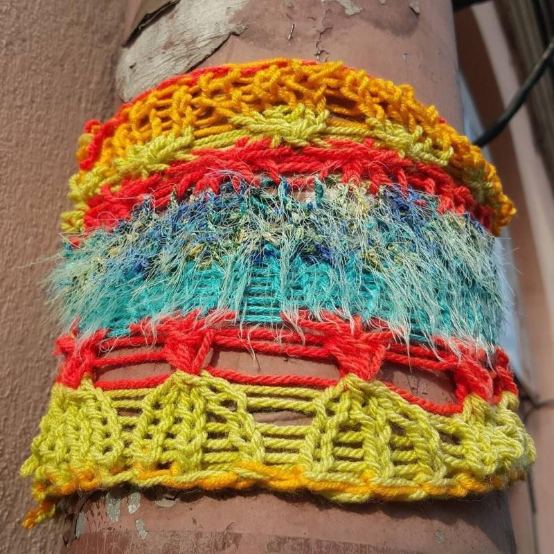 Wielobarwny street art wykonany techniką yarn bombing