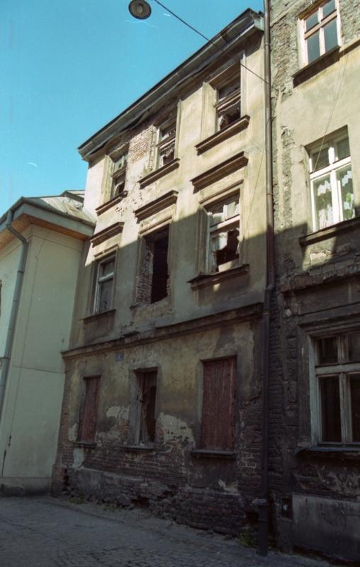z lewej ulica, z prawej fasady kamienic, samochód osobowy