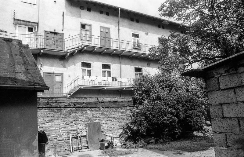 w środku podwórze, z prawej mur z pustaków, za nim drzewo, z lewej naroże budynku, w tle mur działowy, nad nim dwa piętra budynku