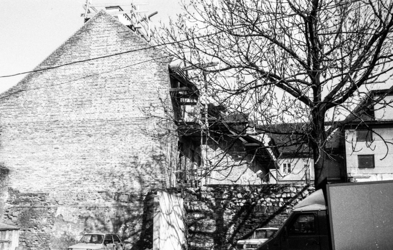 courtyard tenement, on the right fragment of delivery van, behind tree, gable wall of an outhouse, above high-voltage cables