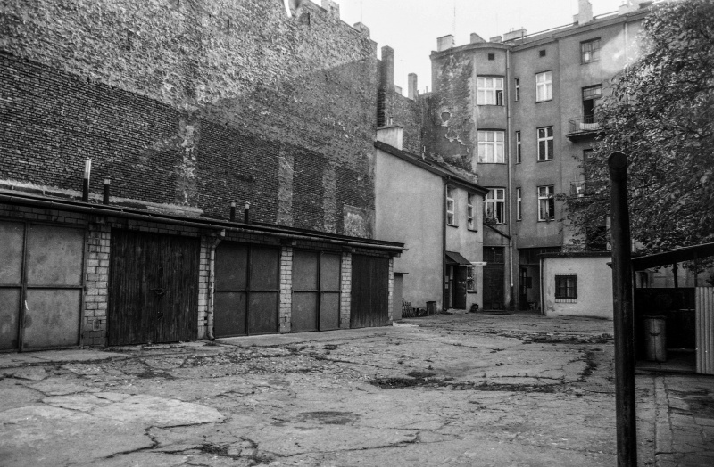 courtyard, on the left garages, above blank wall of an outhouse, in the background tenements, on the right trash can and pole, tree branches