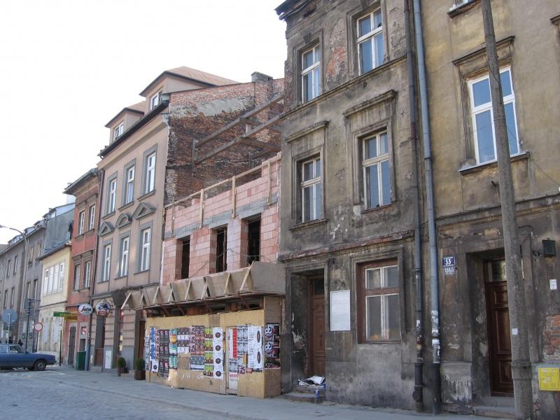 Zachodnia pierzeja ul. Szerokiej, zaniedbane budynki, prace budowlane w miejscu wyburzonego budynku