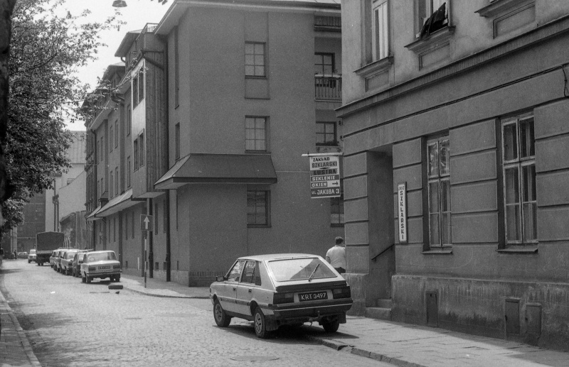 on the left fragment of wall, street, on the right car, building in the street