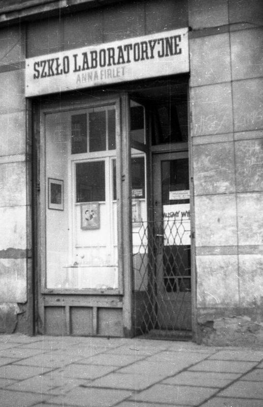 na dole chodnik, witryna i wejście do zakładu: