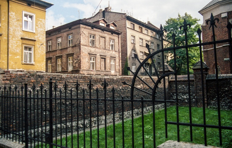 Metal rod fence, street-facing wall, tenement in the background